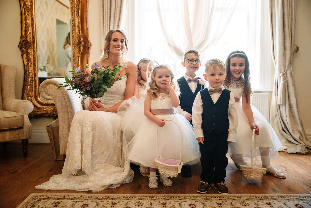 Bride, flowergirls & pageboys on the chaise longue in the bridal suite at West Tower on a spring day
