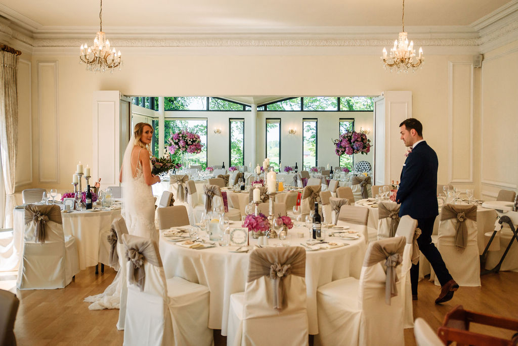 Bride & groom looking at the Ballroom set for their spring wedding breakfast at West Tower