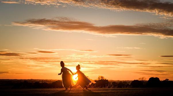 Children running across field in sunset in West Tower ground