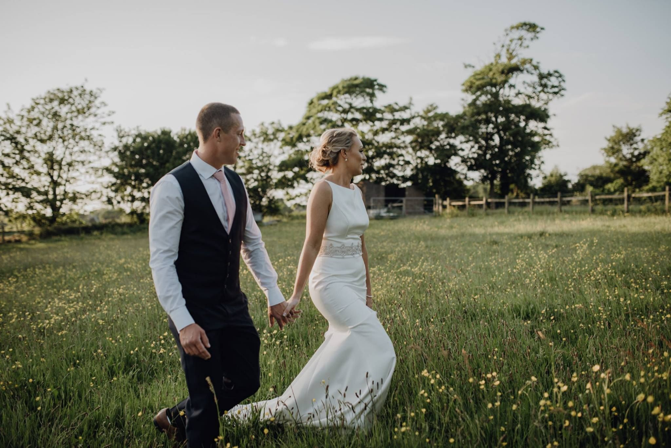 Bride and Groom Strolling through Meadow at West Tower